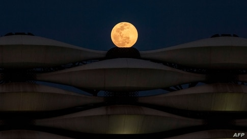"""TOPSHOT - This picture taken on March 28, 2021 shows a view of the rising full """"Worm Moon"""" above Basra International Stadium in…"""