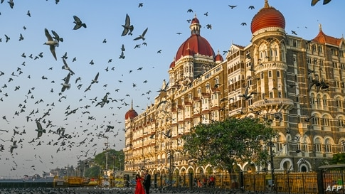 TOPSHOT - A couple poses for photographs in front of the Taj Mahal hotel in Mumbai on March 4, 2021. (Photo by Punit PARANJPE /…
