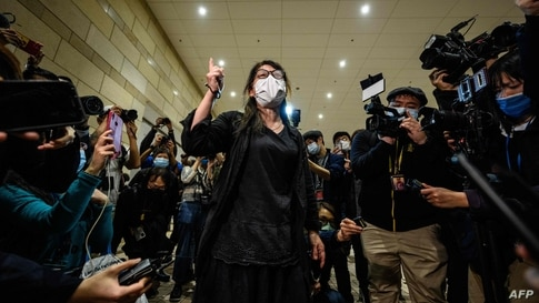 TOPSHOT - A woman (C) reacts while being surrounded by members of the media outside the West Kowloon Court in Hong Kong on…