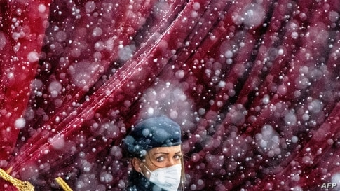 TOPSHOT - Snow falls as a police officer stands guard near the Grand Hotel in Vienna on April 6, 2021, where diplomats of the…