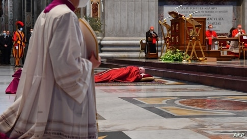 TOPSHOT - Pope Francis (Rear) lies down in prayer prior to celebrate Good Friday Mass for the Passion of the Lord on April 2,…