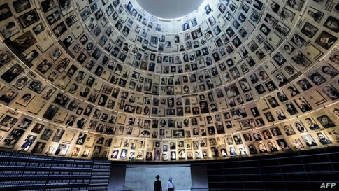 TOPSHOT - Visitors walk from the Hall of Names at Yad Vashem, the Holocaust remembrance centre, on the eve of the ceremonies…