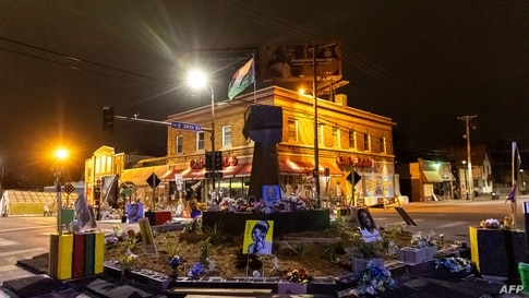 """TOPSHOT - A Black Power fist statue, flag and flowers adorn """"George Floyd Square"""", April 5, 2021 in Minneapolis, Minnesota. -…"""