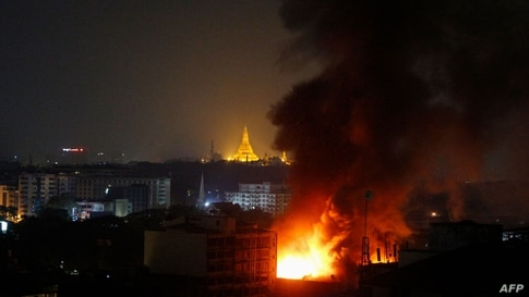 TOPSHOT - Smoke rises from a fire at Ruby Mart in Yangon in the early morning of April 1, 2021 with the Shwedagon Pagoda seen…