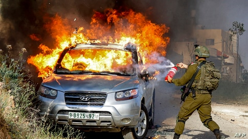 TOPSHOT - An Israeli soldier tries to extinguish flames in a burning Palestinian vehicle during a security operation in the…