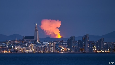 TOPSHOT - The skyline of the Icelandic capital Reykjavik is seen with the glow from the lava coming out of a fissure near the…