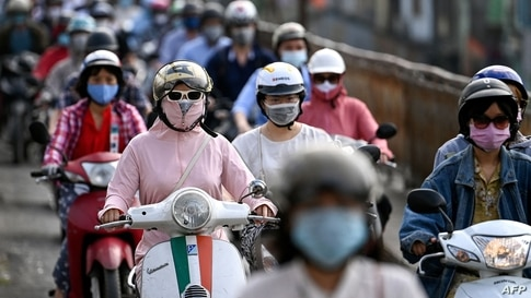 TOPSHOT - Morning commuters wearing face masks, amidst concerns about the Covid-19 coronavirus, ride past in Hanoi on May 4,…