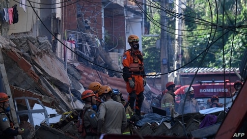 TOPSHOT - Firefighters and rescue teams look for victims of an early morning building collapse at the Rio das Pedras favela in…