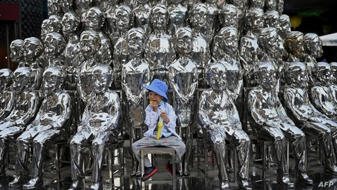 TOPSHOT - A boy sits on a chair amongst sculptures on display at a shopping centre on International Children's Day in Beijing…
