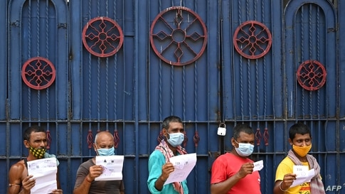 TOPSHOT - Workers hold documents as they wait for their turn to receive the first dose of Covishield vaccine against the Covid…