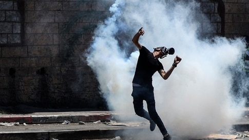 TOPSHOT - A Palestinian demonstrator returns a tear gas canister fired by Israeli security forces during clashes with them…