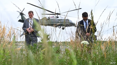 TOPSHOT - US Secret Service agents turn away from the rotor wash as Marine One with US President Joe Biden aboard lifts off…