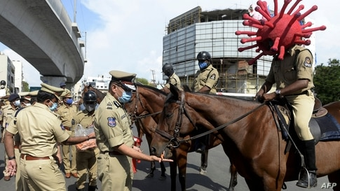 TOPSHOT - A police personnel (R) wearing a Covid-19 coronavirus-themed helmet sits on his horse as he takes part in an…
