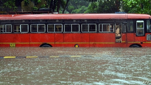 TOPSHOT - A driver looks out from inside a bus stuck in a waterlogged road during a heavy monsoon rainfall in Mumbai on June 9,…