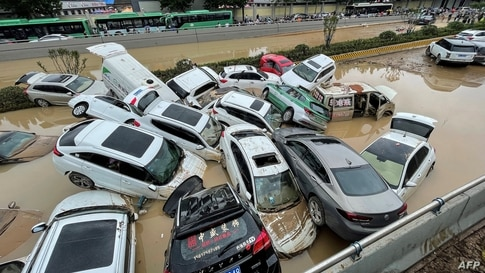 TOPSHOT - Cars sit in floodwaters after heavy rains hit the city of Zhengzhou in China's central Henan province on July 21,…