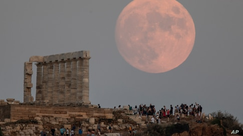 The moon rises behind the columns of the ancient marble Temple of Poseidon at Cape Sounion, about 70 Km (45 miles) south of…