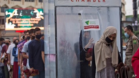 Muslims queue up to enter a disinfection chamber set up as a precaution against the new coronavirus outbreak, prior to entering…