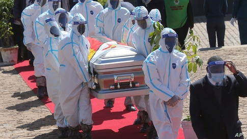Health officials carry the coffin of Zimbabwean minister Perence Shiri, who died of Covid-19, during his burial in Harare,…