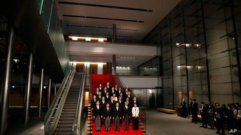 Japan's Prime Minister Yoshihide Suga, front center, and his cabinet ministers pose for a photo session at Suga's official…