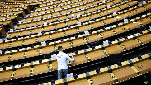 A member of the cleaning crew sanitizes desks in the plenary chamber at the European Parliament in Brussels, Wednesday, Sept…