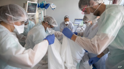 Medical workers tend a patient affected with the COVID-19 in the Nouvel Hospital Civil of Strasbourg, eastern France, Tuesday,…