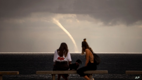 People look at a funnel cloud formed near the beach in Barcelona, Spain, Monday, Sept. 21, 2020. (AP Photo/Emilio Morenatti)