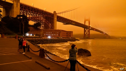 People stop at Fort Point to take morning pictures of the Golden Gate Bridge covered in smoke from wildfires Wednesday, Sept. 9…