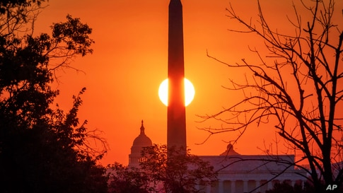 The sun rises behind the Washington Monument on the last day of summer in Washington, Monday, Sept. 21, 2020. The Autumn…