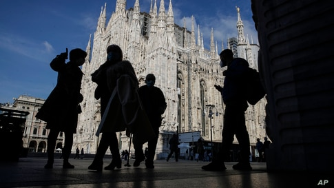 People wear masks to curb the spread of COVID-19 as they walk next to the Duomo gothic cathedral, in Milan, Italy, Friday, Oct…