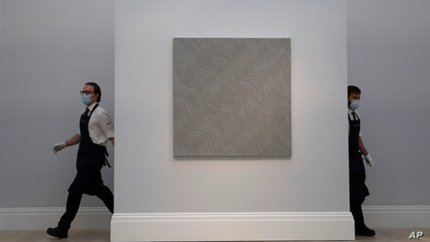 Two members of staff at Sotheby's auction house walk past a painting by Bridget Riley entitled 'Diagonal Curve' in London,…