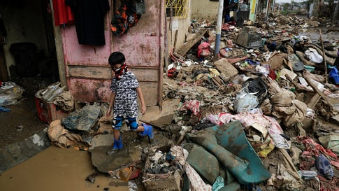 A young resident negotiates a road full of muddied belongings damaged by floods a week ago as Typhoon Vamco hit the area of…