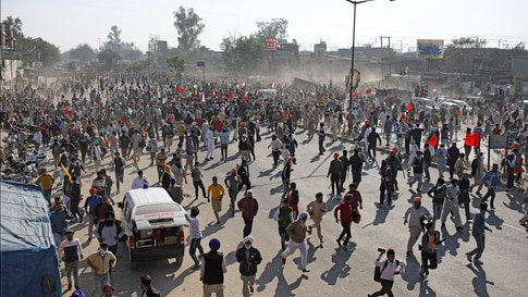 Protesting farmers run for cover as police use water cannon to disperse them, as they attempt to move towards Delhi, at the…