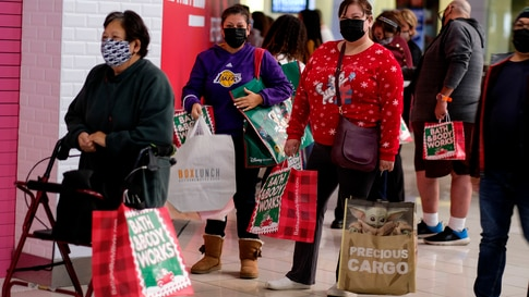 Black Friday shoppers wearing face masks wait in line to enter a store at the Glendale Galleria in Glendale, Calif., Friday,…