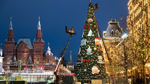 Municipal workers on cranes set up a Christmas tree in Red Square, with the Historical Museum, left, and the GUM State…