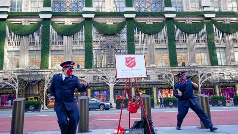 Salvation Army Cadets Cameron DeMatteo, left, and Austin Oberg entertain Black Friday shopper across the street form the Saks…
