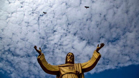Birds fly over a statue of Jesus Christ outside a church on the eve of Christmas in Gauhati, India, Thursday, Dec. 24, 2020…