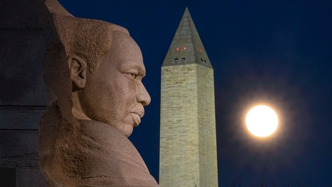 The rising full moon passes behind the Martin Luther King Memorial and the Washington Monument, Tuesday evening, Dec. 29, 2020,…