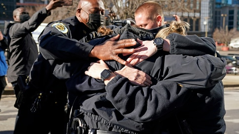Nashville Police Chief John Drake, left, joins a group of police officers as they embrace after speaking at a news conference…