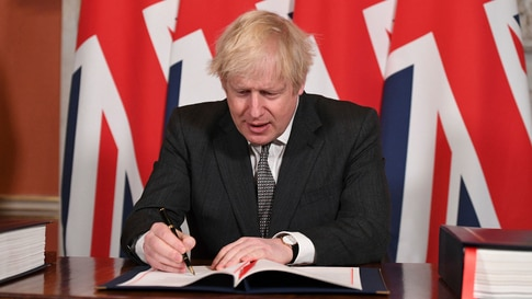 Britain's Prime Minister Boris Johnson signs the EU-UK Trade and Cooperation Agreement at 10 Downing Street, London Wednesday…