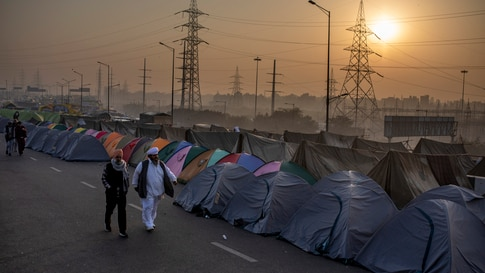 Farmers walk past tents put up in the middle of a major highway which is blocked in a protest against new farm laws at the…