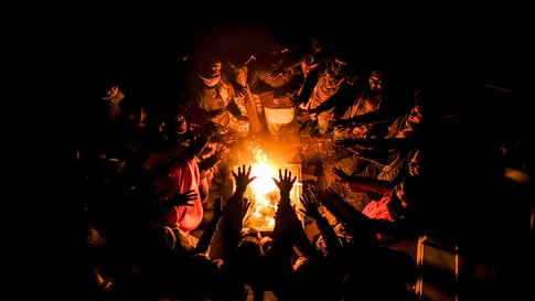 Migrants stretch their hands above a fire at the Lipa camp outside Bihac, Bosnia, Wednesday, Dec. 30, 202, after hundreds…