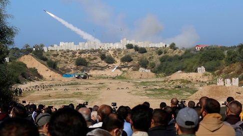 Palestinian militants watch a rocket fired during a military drill organized by military factions outside Gaza City, Tuesday,…