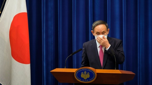 Japan's Prime Minister Yoshihide Suga adjusts a face mask after a press conference on the COVID-19 situation in Japan at the…