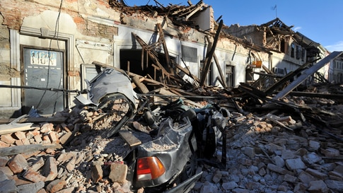 A view of remains of a car covered by debris and buildings damaged in an earthquake in Petrinja, Croatia, Tuesday, Dec. 29,…