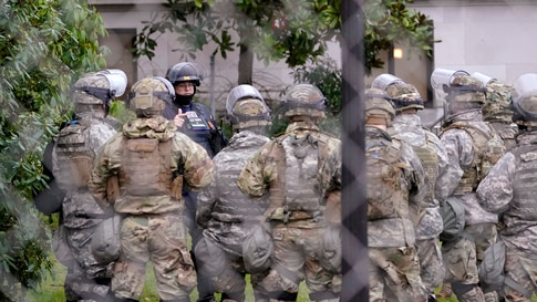 A Washington State Patrol trooper talks with members of the Washington National Guard inside a fence surrounding the Capitol in…