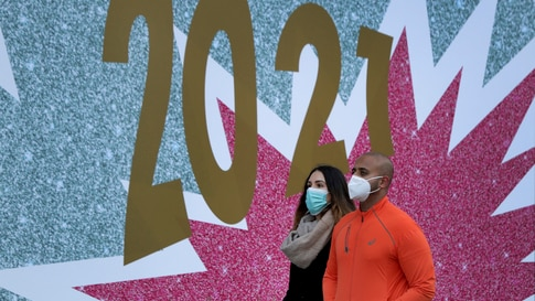 People wear face masks as they walk past the 'KaDeWe' department store in Berlin, Germany, Thursday, Dec. 31, 2020. Germany is…