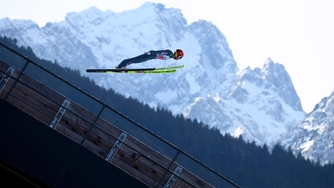 Philipp Aschenwald of Austria soars through the air, with Germany's highest mountain, the Zugspitze, in the background, during…