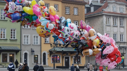 A balloon vendor waits for customers in usually bustling Warsaw's Castle Square that has few people now under anti-COVID-19…