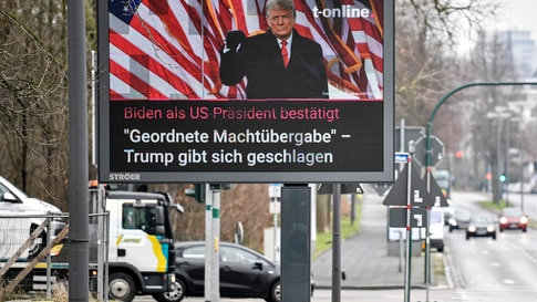 A large news screen beside a street in Essen, Germany, showing US president Donald Trump, and a headline reading 'Biden as US…