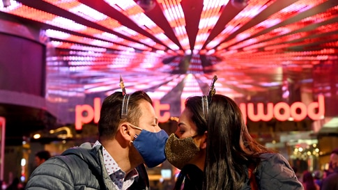 A couple wearing face masks kisses as they celebrate New Year's Eve along the Las Vegas Strip Thursday, Dec 31, 2020, in Las…